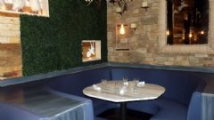 Booth inside Savoie Restaurant with artificial boxwood hedge on wall.